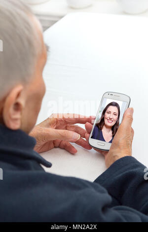 Senior person sitting with her smartphone at a table looking at a photo of her beloved granddaughter, modern lifestyle concept - Stock Image