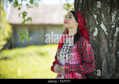 Young woman in traditional russian clothes standing under a tree and looking up - middle shot - Stock Image