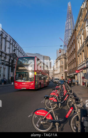 London TFL Santander sponsored line of red rental hire bikes in Southwark Street with red London bus and The Shard building behind. Bike terminal docking station. Transport for London Southwark London UK - Stock Image
