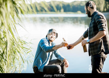 Two fishermen relaxing together with beer while fishing on the lake at the morning - Stock Image