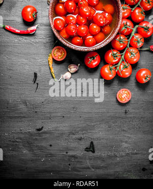Pickled tomatoes in a bowl. On black background. - Stock Image
