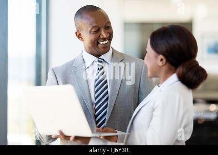 friendly African vehicle dealership principal and saleswoman working on laptop - Stock Image