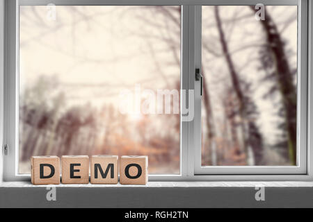 Demo sign in a window with a view to a forest in the morning - Stock Image