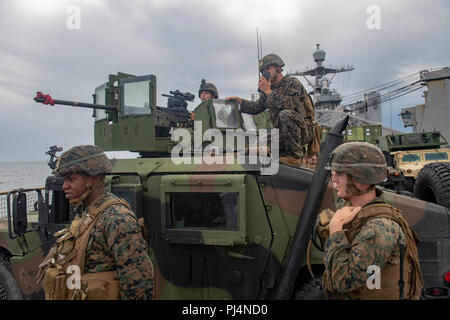 180828-N-AT530-0734 ATLANTIC OCEAN (Aug. 28, 2018) – Marines from the 22nd Marine Expeditionary Unit scan the horizon while participating in an exercise on the amphibious dock landing ship USS Fort McHenry (LSD 43) during Carrier Strike Group FOUR (CSG 4) Amphibious Ready Group, Marine Expeditionary Unit exercise (ARGMEUEX). Kearsarge Amphibious Ready Group and 22nd Marine Expeditionary Unit are enhancing joint integration, lethality and collective capabilities of the Navy-Marine Corps team through joint planning and execution of challenging and realistic training scenarios. CSG-4 mentors, tra - Stock Image