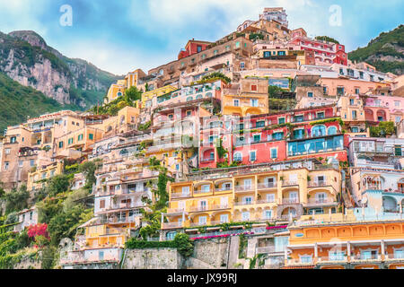 Vibrant pastel colors of cliffside houses and gardens on the waterfront in Positano, Italy. Viewed from the sea. - Stock Image