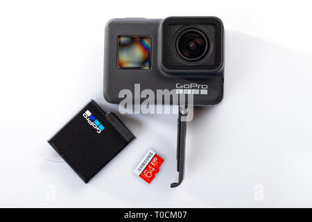 Detail of the correct way to insert the battery and the memory card into the new GoPro Hero 7 Black isolated on white. - Stock Image