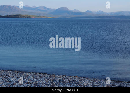 A view from Badentarbat Bay, Scotland, across the sea to the Torridon mountain range on a still clear summer's evening - Stock Image
