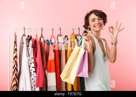 Image of a beautiful woman stylist posing isolated over pink wall background near a lot of clothes holding shopping bags showing okay gesture. - Stock Image