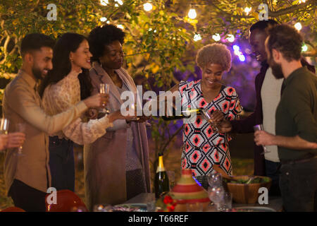 Friends celebrating, drinking champagne at dinner garden party - Stock Image