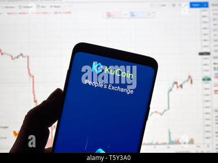 MONTREAL, CANADA - APRIL 26, 2019: Kucoin, cryptocurrency exchange logo and application on Android Samsung Galaxy s9 Plus screen in a hand over a lapt - Stock Image