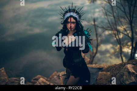 A young woman in the image of a fairy and a sorceress standing next to rocks over a lake with the reflection of the clouds in a black dress and a crow - Stock Image