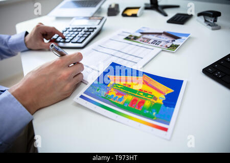 Close-up Of Person Hand Calculating Heat Temperature Using Calculator On Desk - Stock Image