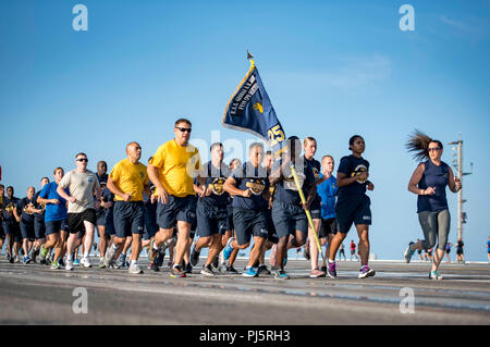 180826-N-SO730-0099 ATLANTIC OCEAN (Aug. 26, 2018) Chief petty officer selectees assigned to the aircraft carrier USS George H.W. Bush (CVN 77) prepare to turn a corner during a 5k fun run on the flight deck. The ship is underway conducting routine training exercises to maintain carrier readiness. (U.S. Navy photo by Mass Communication Specialist 3rd Class Joe Boggio) - Stock Image