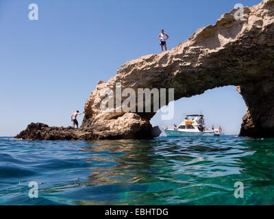 Tourists on and around the natural stone bridge at the sea caves just outside Ayia Napa, Cyprus. - Stock Image