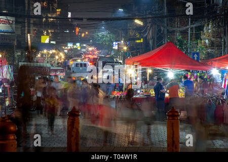 Long exposure motion night time image of a Loas night market. - Stock Image