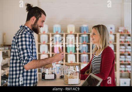Young male shop assistant serving a female customer in a zero waste shop. - Stock Image