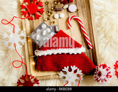 Top view of different pills vitamins as a Christmas gift in slipper stocking on vintage wooden tray with felt snowflakes as decoration. Gift idea conc - Stock Image