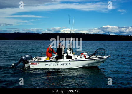 Female angler & fishing guide holding chinook salmon in 20-foot Boston Whaler Outrage boat Painter's Lodge - Stock Image