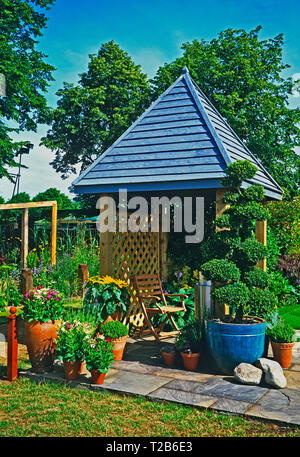 A colourful urban garden with planted containers of flowers and a cloud pruned topiary tree with covered seating area - Stock Image