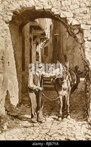 Man and donkey in a street in Puget-Theniers, Alpes-Maritimes, France. - Stock Image