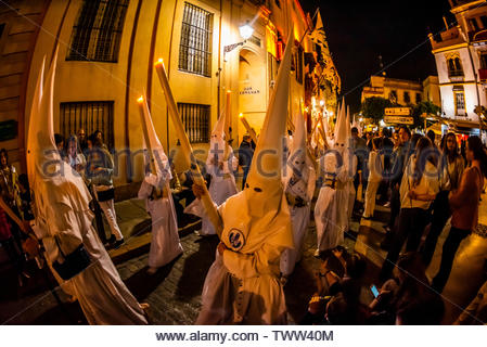 Hooded Penitents (Nazarenos) in the procession of the Brotherhood (Hermandad) La Candelaria, Holy Week (Semana Santa), Seville, Andalusia, Spain. - Stock Image