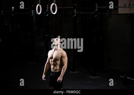 Bare chested young man preparing to use gym rings in dark gym - Stock Image