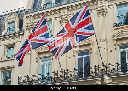 Two flags of Great Britain, commonly called Union Jacks, fly from a building in central London. - Stock Image