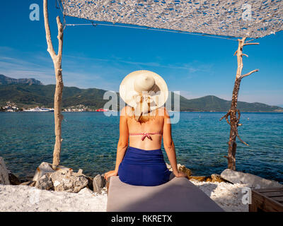 Thasos, Greece. Good looking woman enjoying a day at on a marble beach on a hot summer day - Stock Image