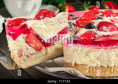 Cheesecake with strawberries, blueberry and jelly on a plate - Stock Image