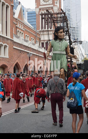 Jean-Luc Courcoult (braces & red trousers), watches keenly as his Little Girl Giant walks through Perth city - Stock Image