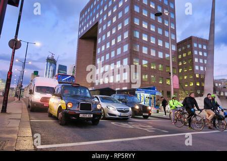 Vehicles and cyclists waiting at traffic lights on London Bridge, London, England, UK - Stock Image