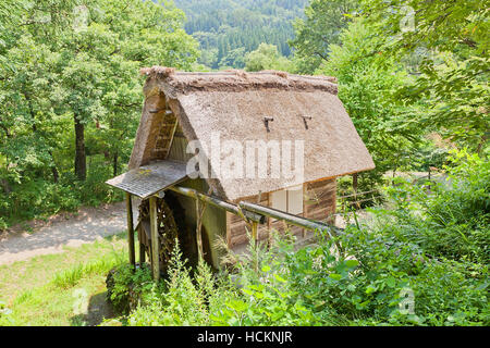 Watermill with gassho style thatched roof (circa 19th c.) in Ogimachi gassho style village. UNESCO site of Japan - Stock Image