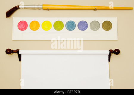 Flipchart and palette with a paintbrush on a wall - Stock Image