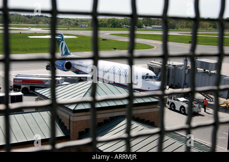Airplane viewed through a security fence at Westchester County Airport, Harrison, NY - Stock Image