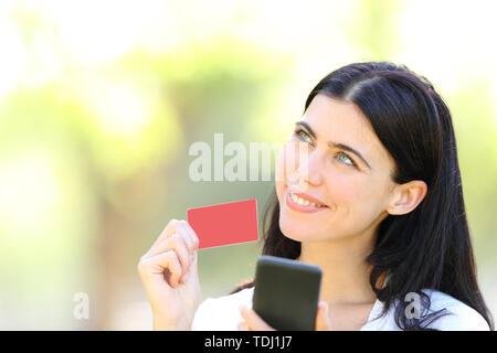 Happy online shopper holding smart phone showing blank credit card and looking at side in a park - Stock Image