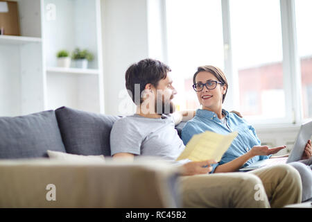Affectionate couple relaxing on sofa and discussing online tours while looking for the best ones - Stock Image