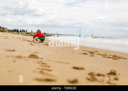 Young child crouching on beachs waters edge digging many small holes in sand, taken from behind. Poole, Dorset, England. - Stock Image