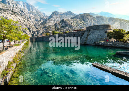 The medieval city walls and moat separating with the mountains and castle behind in the Adriatic ancient city of Kotor, Montenegro. - Stock Image