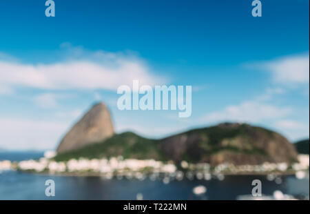 Deliberately defocused abstract view of Sugarloaf Mountain and Rio de Janeiro Brazil skyline reflecting on Botafogo Bay. - Stock Image