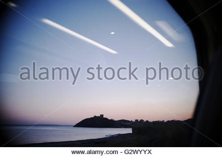 Criccieth Castle seen thru a train carriage window at sunset, in Gwynedd, north Wales, UK. - Stock Image