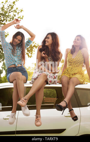 Three girl friends sitting on top of car - Stock Image