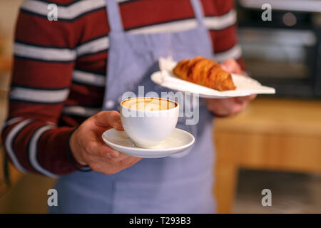Barista serving cappuccino and croissant. Closeup on the man's hand. Selective focus on cappuccino - Stock Image