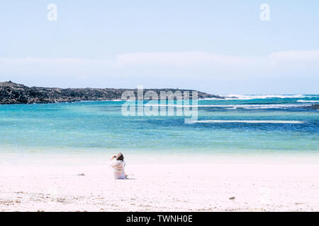 Scenic travel holiday vacation destination concept with white sandy beach and blue ocean and sky and senior woman sit down taking picture of the beaut - Stock Image