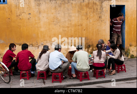 Customers sitting on low plastic stools eating at a street food noodle stall in Hoi An, Viet Nam - Stock Image