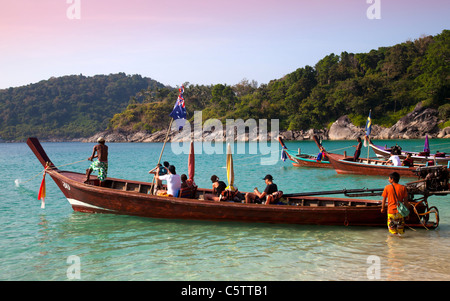 Longtail Boats anchored along Freedom Beach and passengers on board . - Stock Image