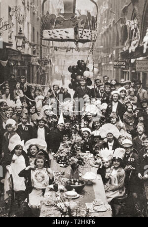 A typical London street tea party.  Children celebrate the Coronation of George VI and Queen Elizabeth in 1937.  From The Coronation in Pictures, published 1937. - Stock Image