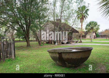 View of a slave cabin with a large iron bowl used for boiling down and refining sugar cane sited in the Whitney Plantation Museum in Louisiana, USA - Stock Image