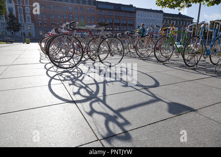 Bicycles for sale on Israels Plads, Israel's Square, Copenhagen, on a Saturday flea market. Long shadows of backlit bicycles. Assembled in  background - Stock Image