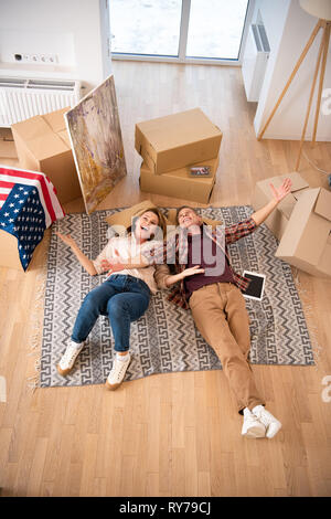 overhead view of happy excited couple laying on floor at new home - Stock Image