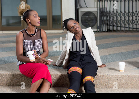 Young women sitting outside their offices take coffee at their break. - Stock Image